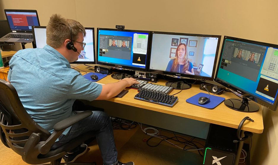 virtual event production worker in front of multiple monitors